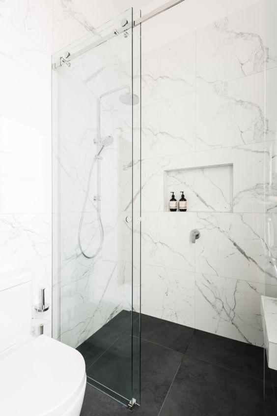 bellissime piastrelle in marmo bianco alle pareti e piastrelle nere opache sul pavimento creano una combinazione elegante e senza tempo