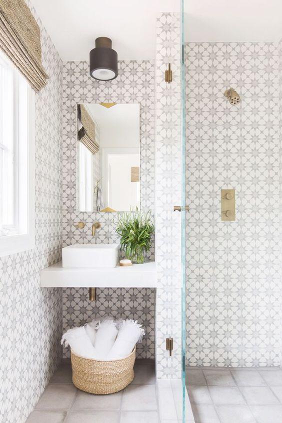 tessere di mosaico a motivi geometrici chic sulle pareti e quelle grigio chiaro neutro sul pavimento più accenti in ottone