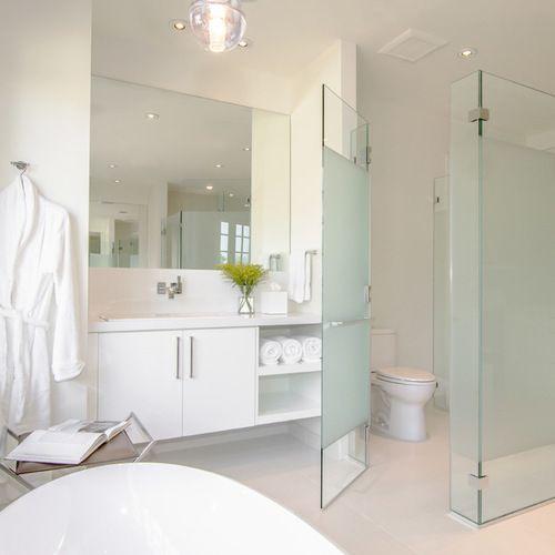 un divisorio per WC in vetro smerigliato blu per una maggiore privacy e persino un tocco colorato allo spazio neutro
