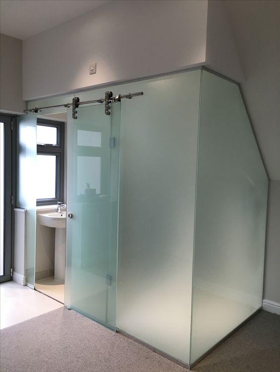 un box bagno rivestito con vetro smerigliato e con una porta scorrevole principale è un'idea audace per uno spazio moderno
