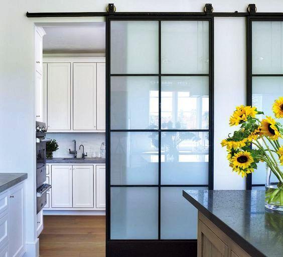porte scorrevoli con cornice nera e vetro smerigliato dividono comodamente la cucina e la sala da pranzo