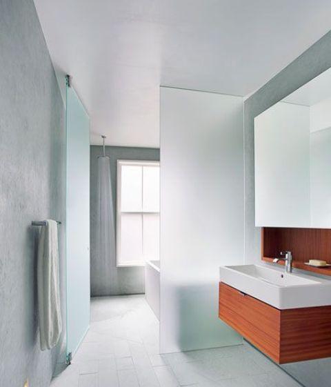 un piano di vetro satinato separa il lato umido del bagno, con doccia aperta, dal lato asciutto