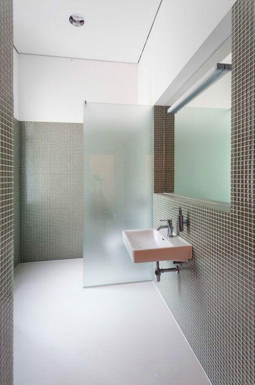 un elegante bagno minimalista con piastrelle grigie e stucco bianco e un divisorio in vetro smerigliato per la toilette