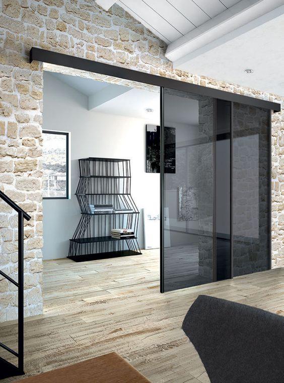 le porte scorrevoli in vetro fumé risaltano nel rivestimento in pietra conferendole un aspetto fresco e più moderno