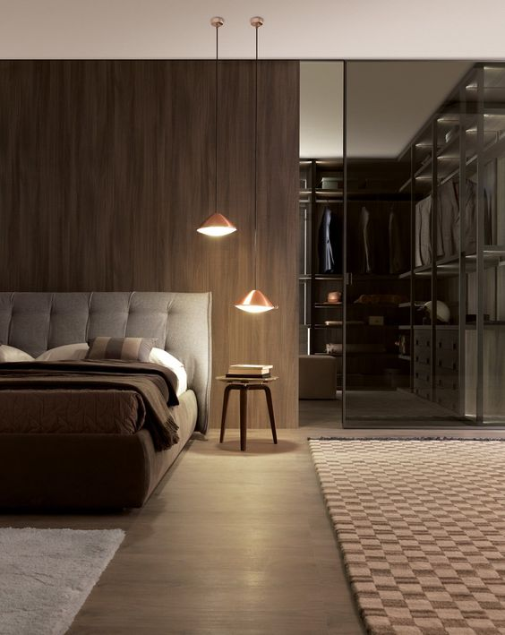 una camera da letto maschile con cabina armadio con parete divisoria in vetro fumé per suddividere sottilmente lo spazio