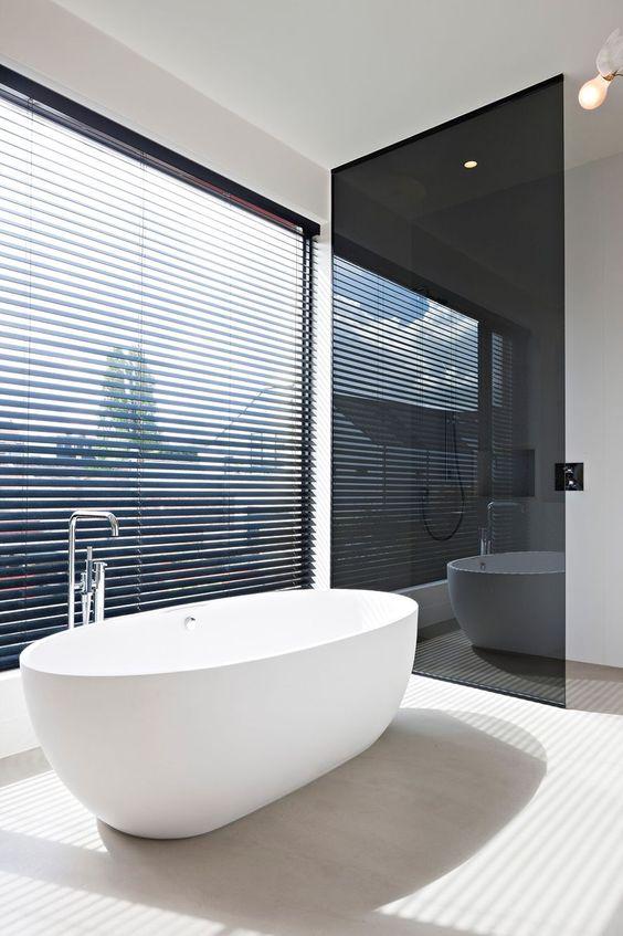 una porta del bagno in vetro fumé offre privacy e non ingombra troppo lo spazio