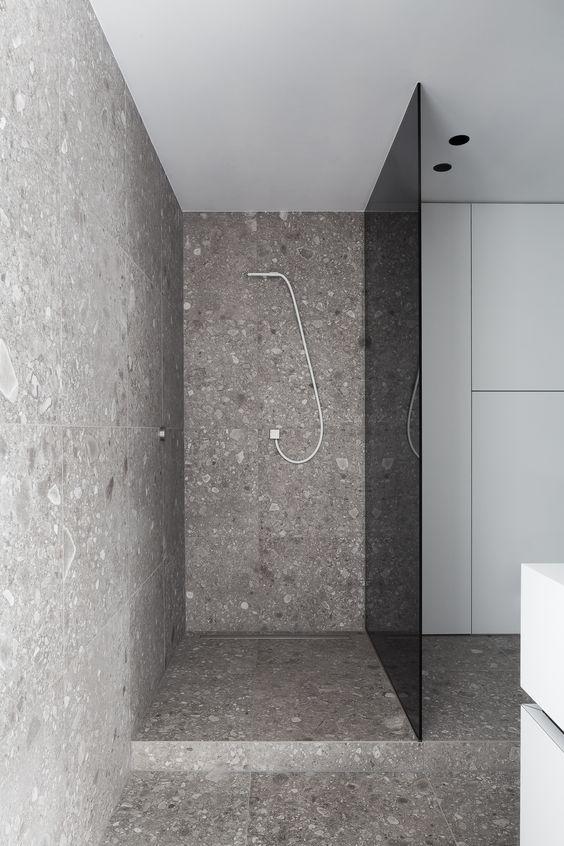 un moderno bagno grigio rivestito con terrazzo e una porta doccia in vetro fumé per la privacy