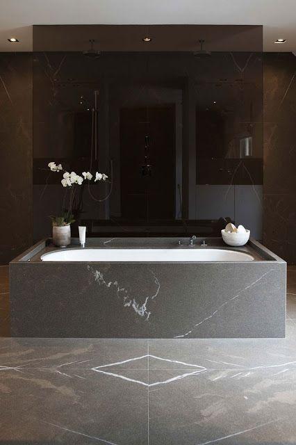 un bagno in marmo nero si sente lussuoso e una doccia in vetro fumé aggiunge stile e un'atmosfera spigolosa