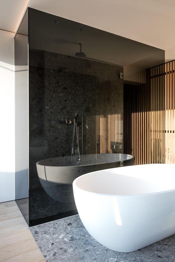 uno spazio contemporaneo con una doccia racchiusa in vetro fumé lo rende separato e più audace