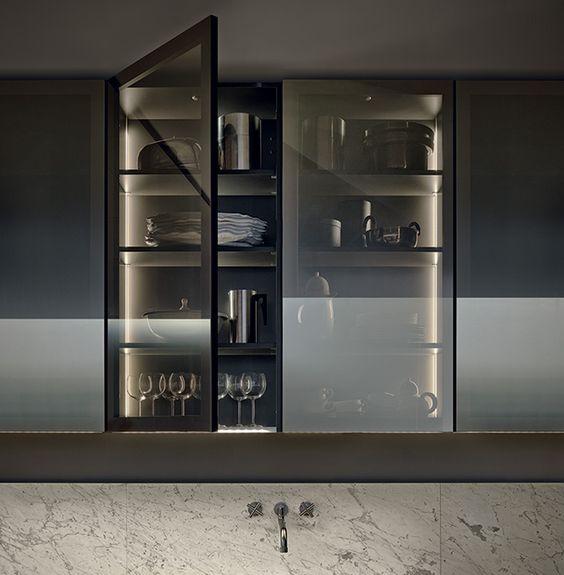 un mobile da cucina con ante in vetro fumé mette in mostra bicchieri e stoviglie ma lo fa con delicatezza