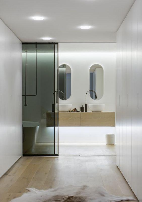 le porte scorrevoli in vetro fumé risaltano in spazi neutri e minimalisti e li dividono ma non troppo