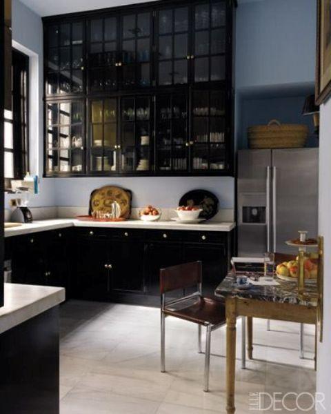 una cucina raffinata con mobili neri e mobili superiori in vetro fumé più controsoffitti bianchi per un contrasto