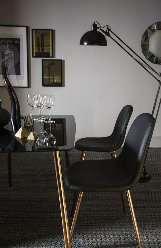 un fantastico tavolo da pranzo di un tavolo in vetro fumé e gambe in rame e sedie in pelle nera con gambe in rame per una sala da pranzo lunatica