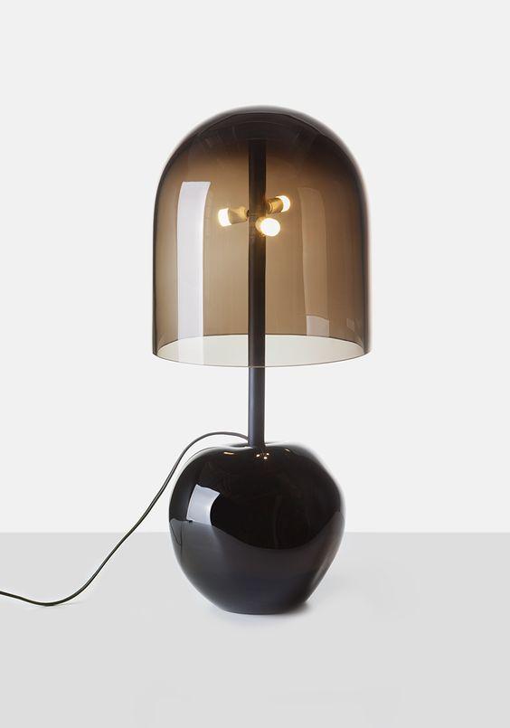 una lampada da tavolo moderna elegante e audace con una base in vetro nero e un paralume in vetro fumé per uno spazio contemporaneo