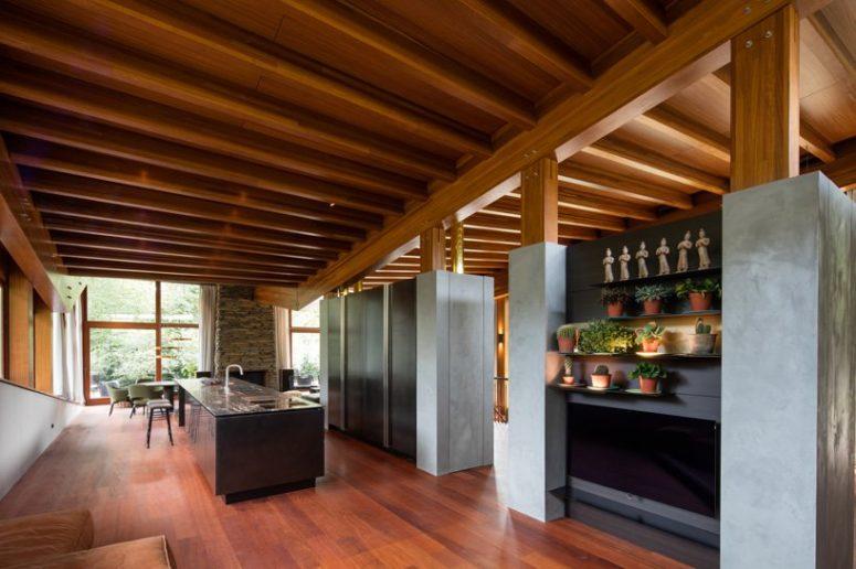 La cucina è contemporanea, con armadi in vetro e cemento, una grande isola cucina e persino un giardino interno