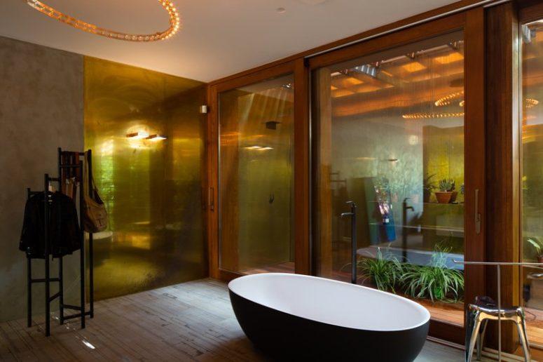 Anche il bagno è dotato di vetri, ma la privacy è mantenuta con un giardino esterno