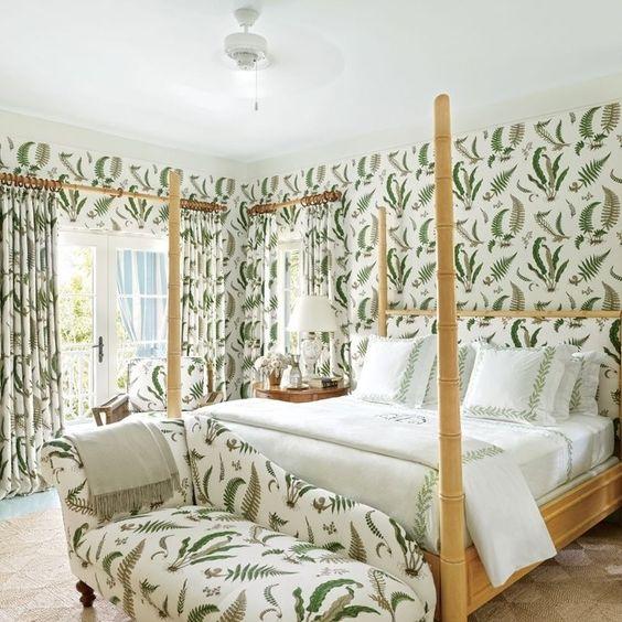 un elegante divano letto ai piedi del letto presenta la stessa stampa delle pareti e delle tende di questa fresca camera da letto femminile