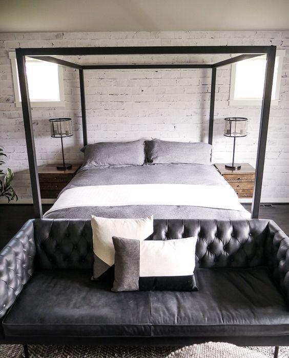 una camera da letto industriale con un divano capitonné in pelle nera ai piedi del letto che aggiunge stile
