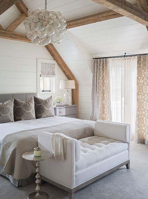 una panca trapuntata cremosa ai piedi del letto è un'idea elegante per uno spazio letto neutro