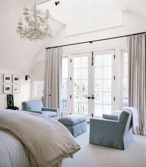 un angolo chic di due sedie blu polvere e un pouf creano un angolo rilassante e aggiungono colore allo spazio