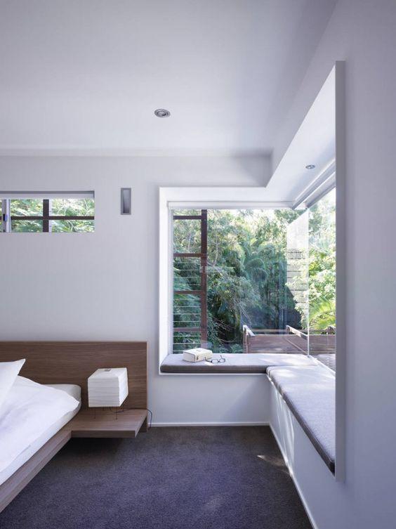 una camera da letto minimalista con un davanzale imbottito come un divano letto o un sedile è una bella idea per catturare il panorama