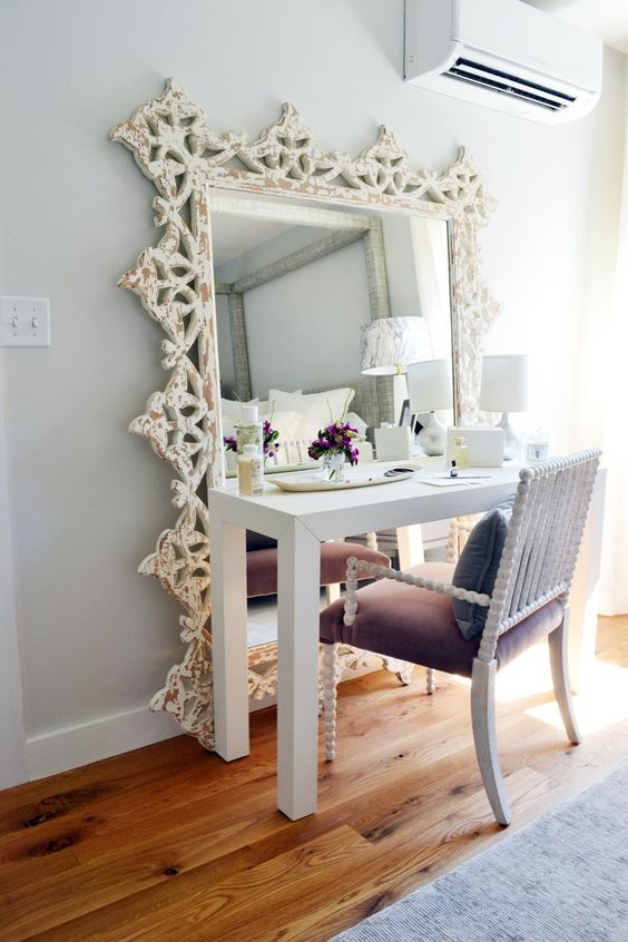 uno spazio di vanità chic con uno specchio di grandi dimensioni e una sedia in velluto viola con gambe curve