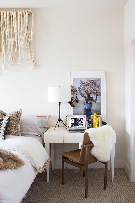 una vanità che funge anche da comodino e un'elegante sedia in legno e pelle con un po 'di pelliccia