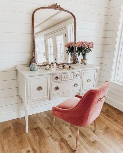 una vanità vintage e una sedia imbottita rosa da esso come un tocco colorato e un pezzo di seduta