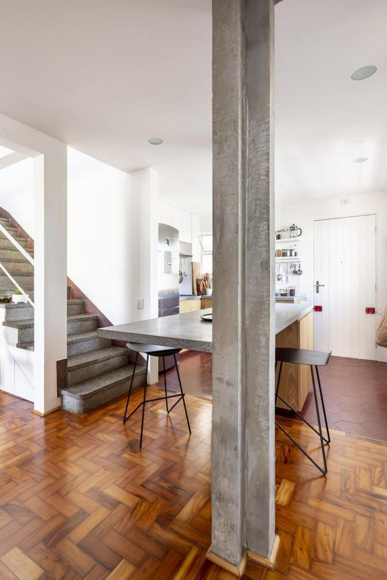 La sala da pranzo funge anche da isola cucina composta da armadi in legno e un piano di lavoro in cemento