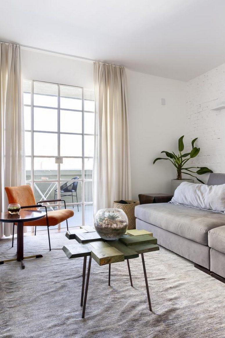 Il soggiorno dispone di alcuni mobili comodi, una sedia arancione brillante e un tavolino da caffè eccentrico