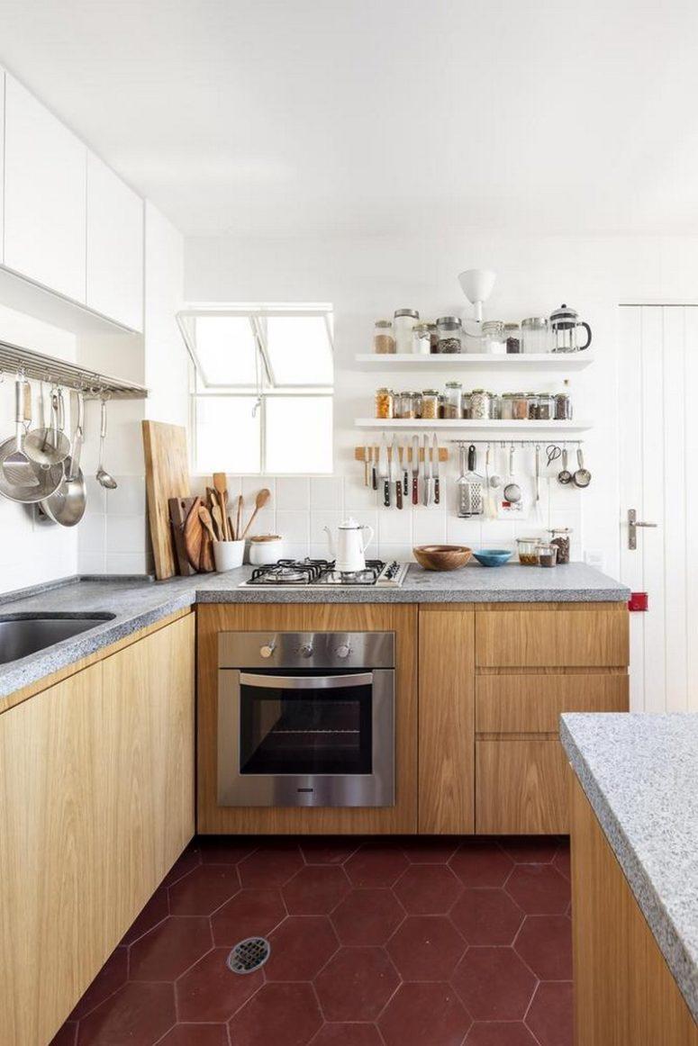 La cucina è realizzata con armadi bianchi e in legno, con ripiani in cemento e un alzatina in piastrelle bianche