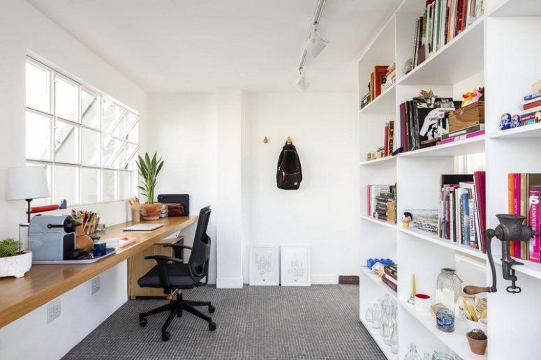 Un ufficio a casa è fatto con un grande contenitore e una scrivania galleggiante vicino alla finestra, la vegetazione in vaso rinfresca lo spazio