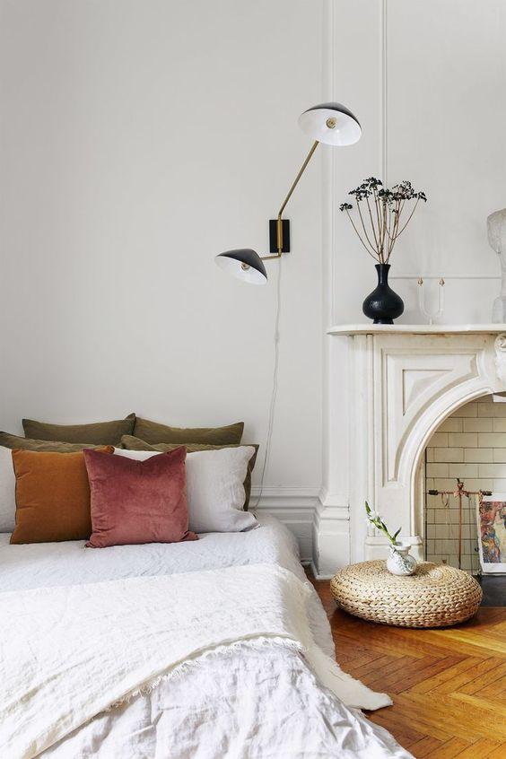 una bella camera da letto parigina con un finto caminetto, lampade art déco, un letto con cuscini smorzati