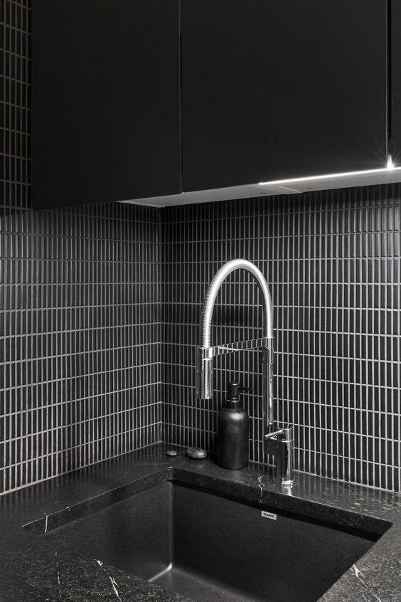 un paraschizzi minimalista nero con piastrelle strette posizionate verticalmente ed evidenziate con malta bianca