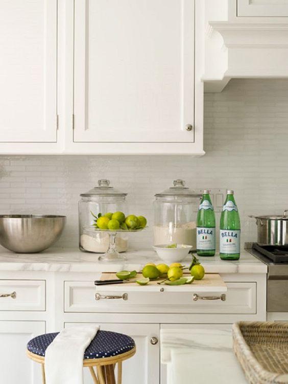 una bella cucina bianca con un backsplash di piastrelle bianche magre che si illumina e si aggiunge all'arredamento della cucina e si abbina alla combinazione di colori