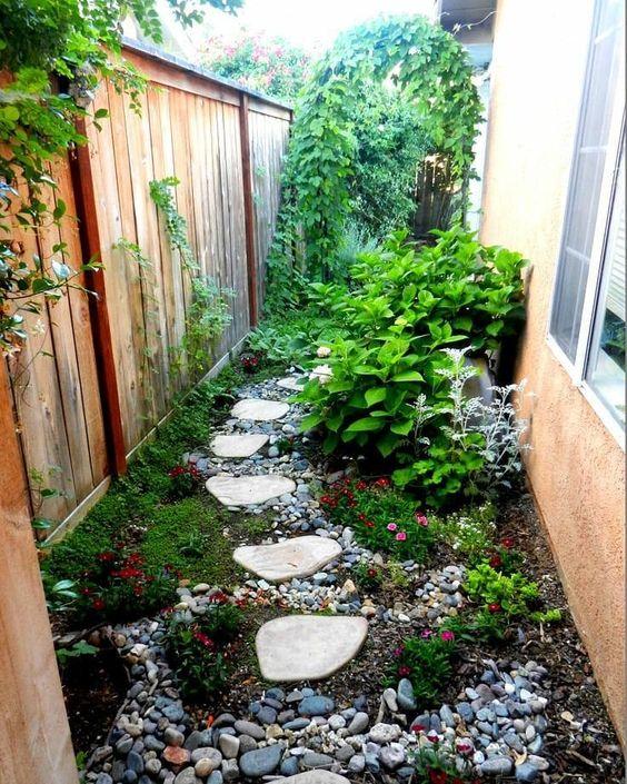 un piccolo e luminoso angolo giardino con ciottoli, piante verdi e fiori luminosi, arbusti e piante rampicanti sul recinto