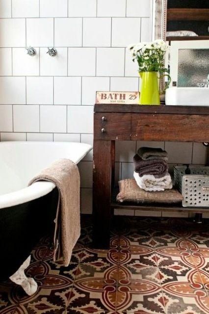 un boho incontra un bagno rustico con piastrelle a mosaico sul pavimento, un lavabo in legno e una grande vasca nera
