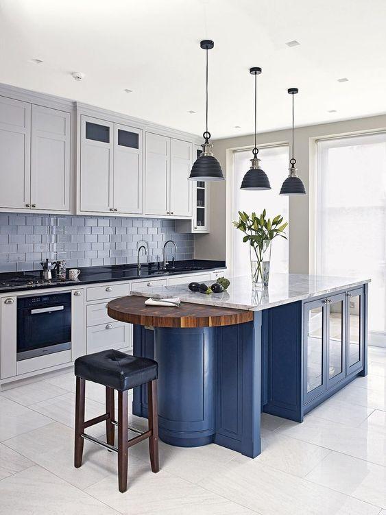 armadi bianchi con piani neri, un'isola cucina blu con un piano bianco e una parte in legno sembrano molto contrastanti