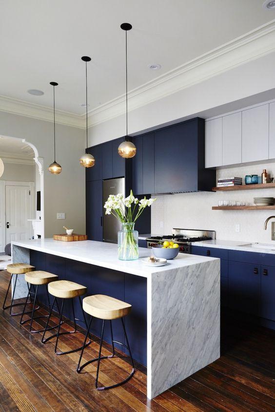 una luminosa cucina blu navy e bianca con piano di lavoro in pietra, lampade a sospensione, sgabelli in legno e alzatina piastrellata bianca