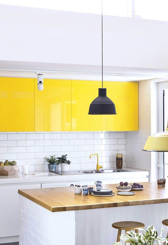un'audace cucina contemporanea in bianco, con mobili superiori giallo brillante, un piano di lavoro in legno e un backsplash in piastrelle bianche della metropolitana