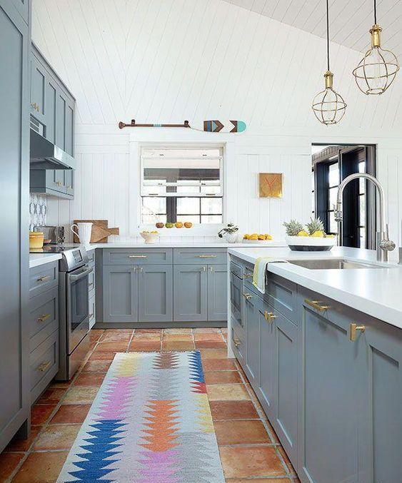 una cucina luminosa con armadi grigi, pareti e ripiani bianchi e tocchi d'oro qua e là