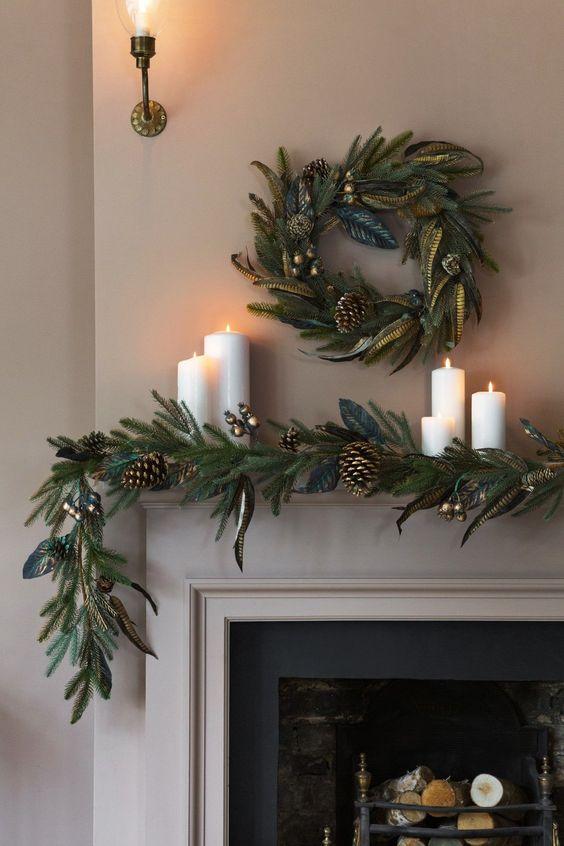 un'elegante ghirlanda sempreverde con tocchi dorati, pigne e una ghirlanda abbinata sulla mensola del camino più candele a colonna