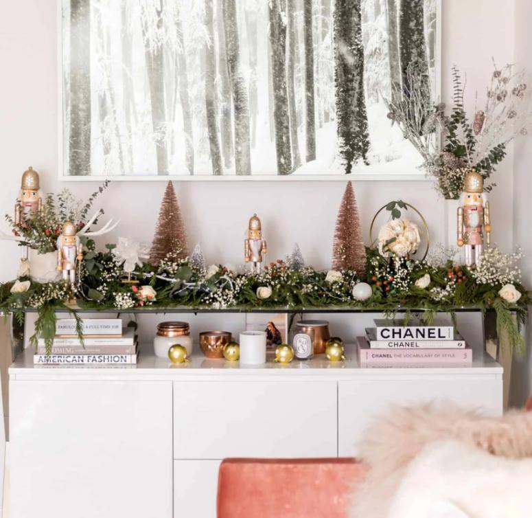 una ghirlanda verde con fiori bianchi e bacche sulla consolle per dare uno spirito festoso al tuo salotto o ingresso