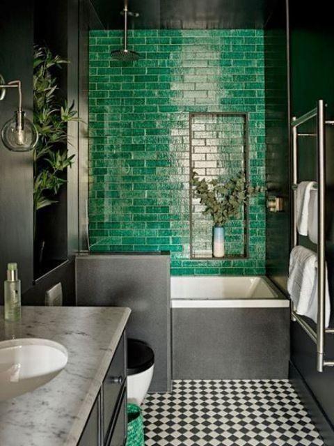 un bagno lunatico con un muro di piastrelle color smeraldo, un pavimento a quadri e un piano di lavoro in marmo sembra super audace