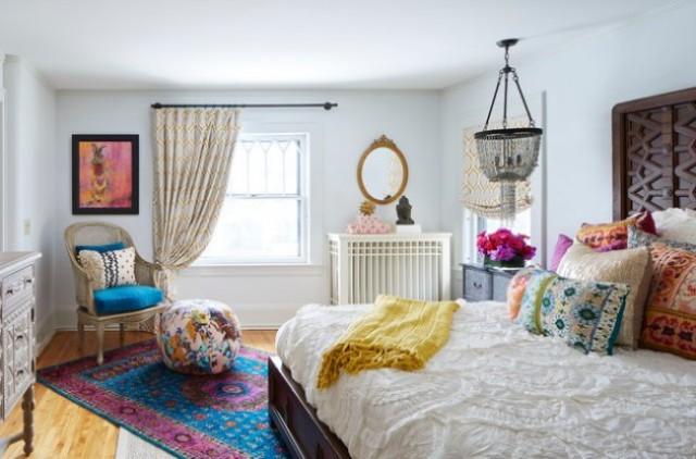 una luminosa camera da letto eclettica realizzata con tessuti stampati colorati, un moderno letto in legno, un lampadario boho e alcune credenze intagliate