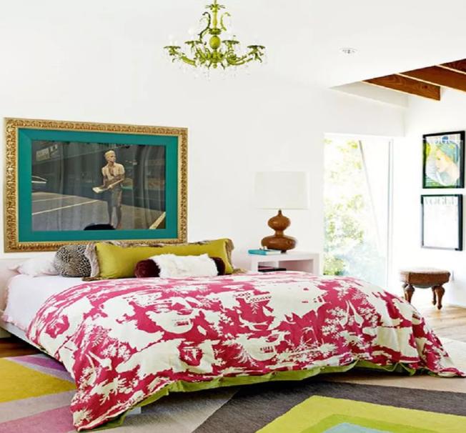 una colorata camera da letto eclettica in un luminoso mix di colori, con opere d'arte audaci e un lampadario boho