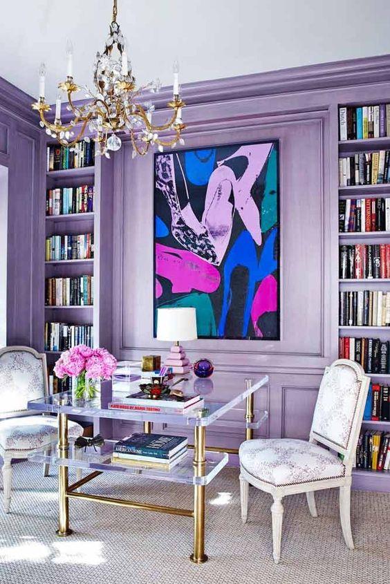 un audace soggiorno glam con pareti lilla e scaffali incorporati e un'opera d'arte luminosa è pieno di colori teneri