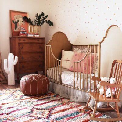 un bellissimo asilo nido boho con un muro a pois, un luminoso tappeto boho, mobili in legno e rattan, un ottomano in pelle, vegetazione e un cactus