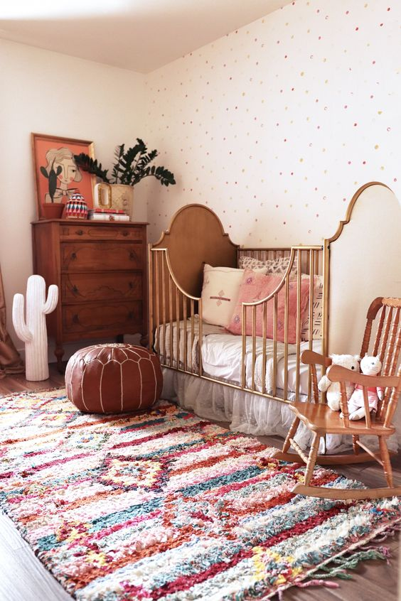 un bellissimo cameretta boho con un muro a pois, un luminoso tappeto boho, mobili in legno e rattan, un ottomano in pelle, vegetazione e un cactus