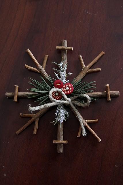 un semplice ornamento a fiocco di neve in stick con sempreverdi, bottoni rossi e spago può essere facilmente realizzato da te o dai tuoi bambini